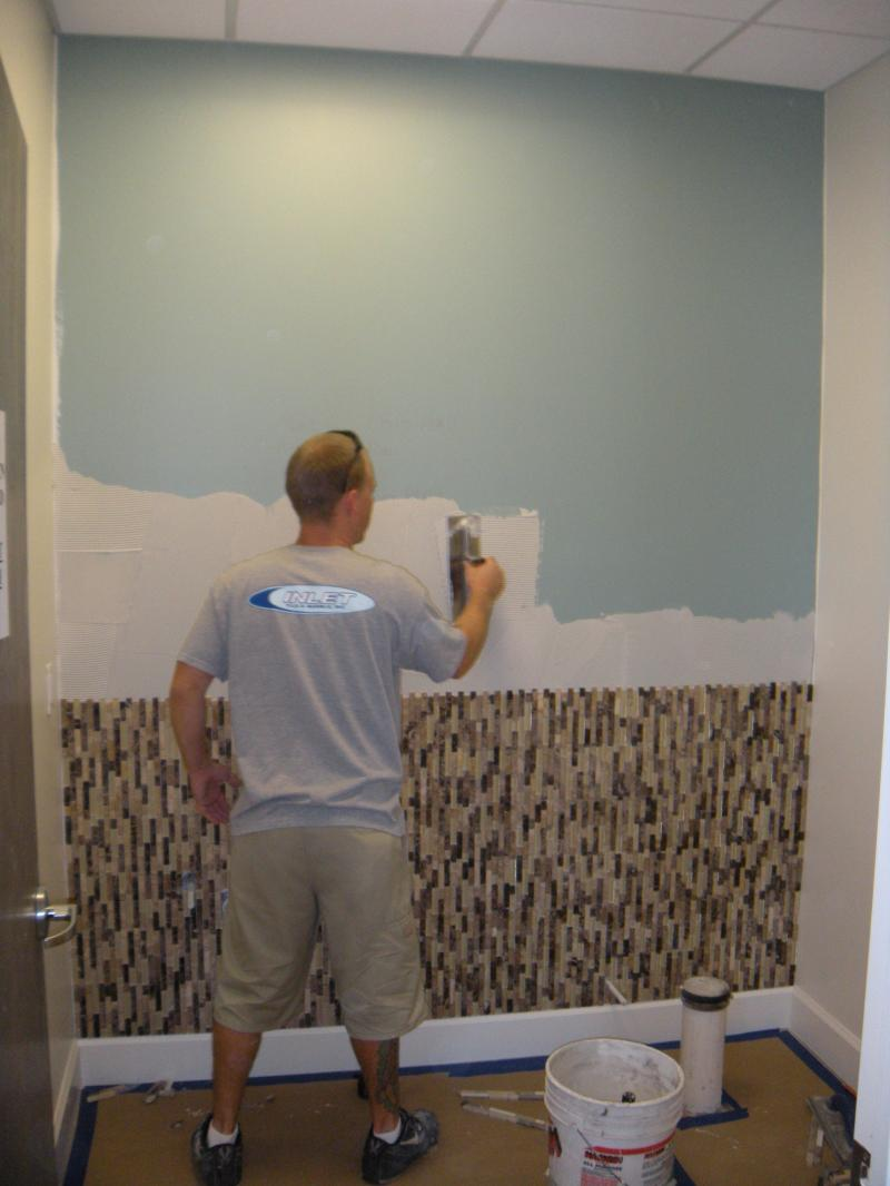 Brandon installing mosaics at medical building - Affinity Construction Group